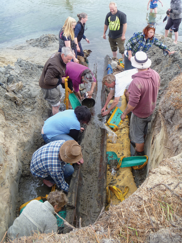 Volunteers lend a hand to extract a prehistoric tōtara waka from a sand dune  at Papanui Inlet in October. It is the second-oldest waka ever found in Aotearoa.