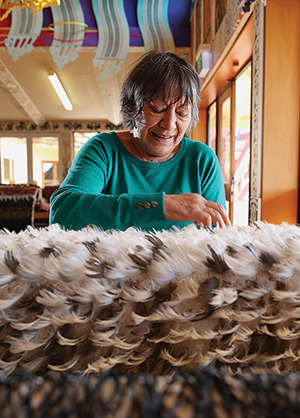 Priscilla Blair working hard on her second whānau korowai.