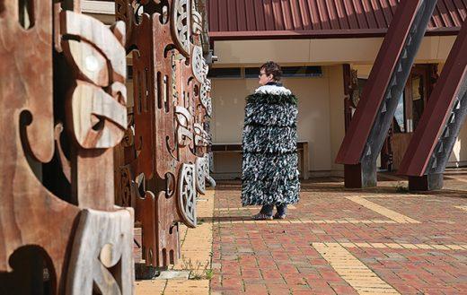 Helen Wilson wearing her completed whānau korowai outside Te Rau Aroha Marae.