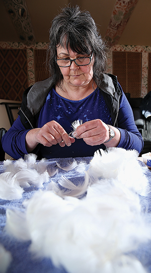 Barbara Metzger preparing feathers for weaving.